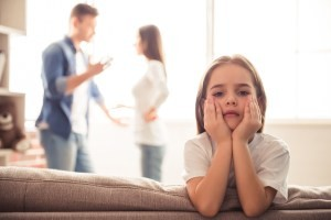 Sad little girl is looking at camera while her parents are arguing in the background